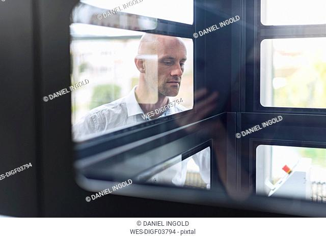 Businessman looking into glass box