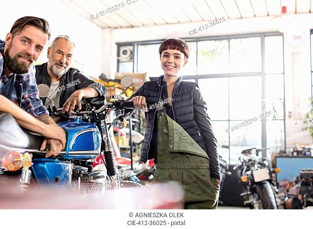 Portrait smiling male and female motorcycle mechanics in workshop