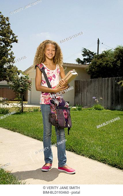 Mixed race girl carrying books
