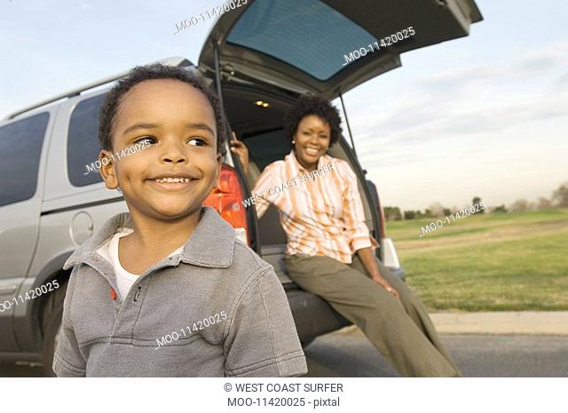 Young boy and mother by open car boot