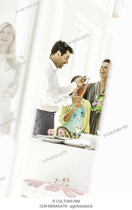 Mature man with wine bottle at family party