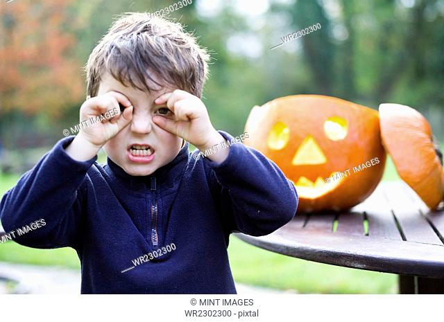 A boy looking through his curved fingers beside a carved pumpkin lantern