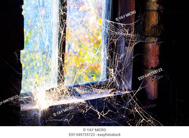 Old window with cobweb around and darkness inside