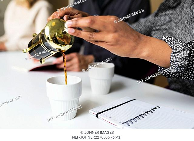 Woman pouring coffee at business meeting
