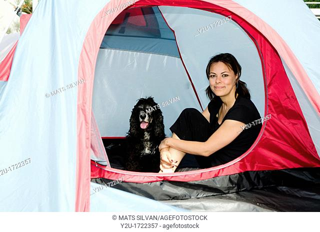 Woman sitting inside a tent with her cocker spaniel dog