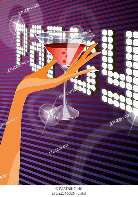 Close-up of a woman's hand holding a martini glass