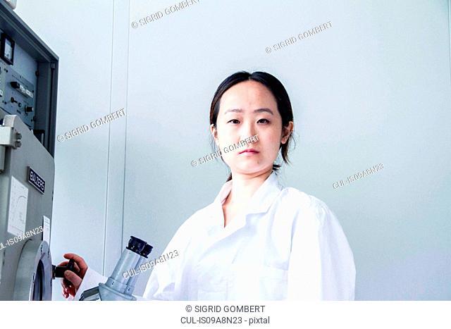 Portrait of female scientist using lab equipment