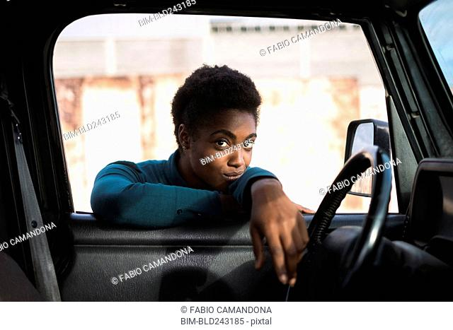 African American woman leaning on car window