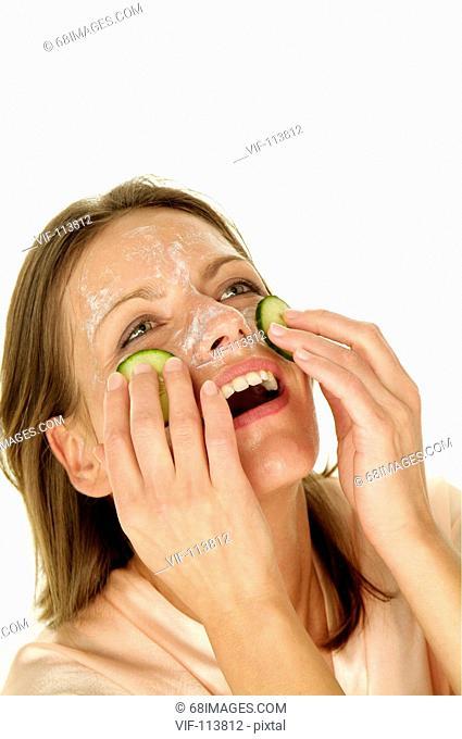 Junge Frau hat SpaÀ bei der Gesichtspflege - Gurkenmaske - K°rperpflege - wellness / Studioaufnahmen / *Model Released* / eingebettetes Farbprofil: ECI-RGB