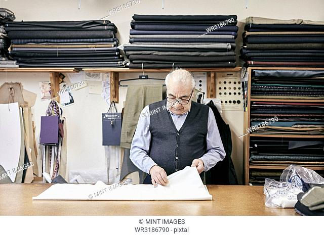 Man inspecting fabric in family-run tailor business