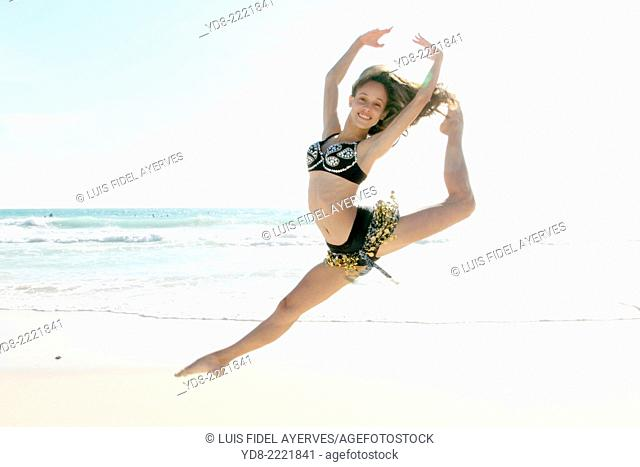 Young woman doing ballet jumping on the beach in Miami Beach, Florida, USA