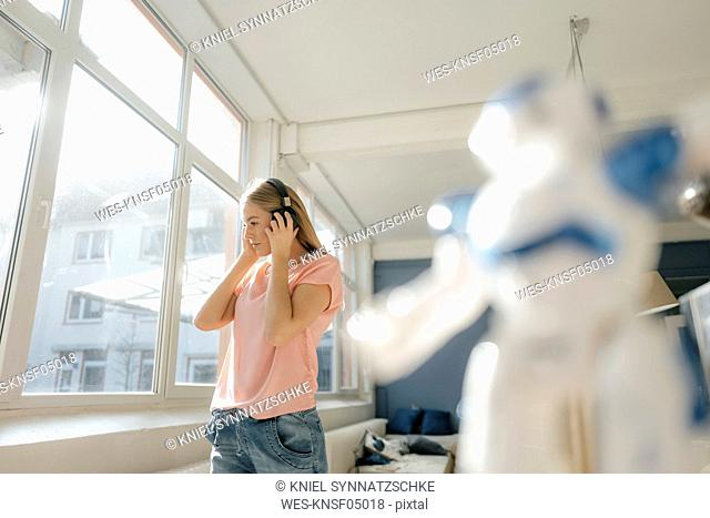 Young woman listening music with headphones at home