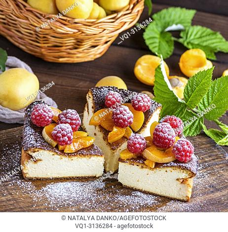 pie with raspberries and apricots on a brown wooden board, close up