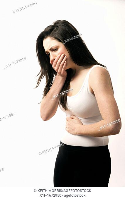 A young woman with brown hair and eyes feeling ill sick nauseous
