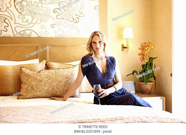 Woman drinking wine in elegant bedroom