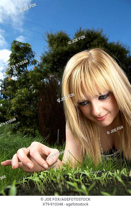 young blonde haired woman late teens early twenties tending a tray of parsley herb seedlings in a garden
