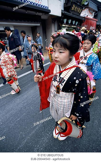 10-12 year old girls called tekomae in traditional kimono walking in front of dashi or wagons during the July Gion Matsuri