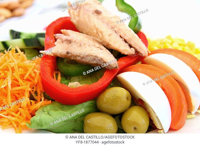 Salad with tuna fish, lettuces, boiled egg, olives, carrot and tomatoes