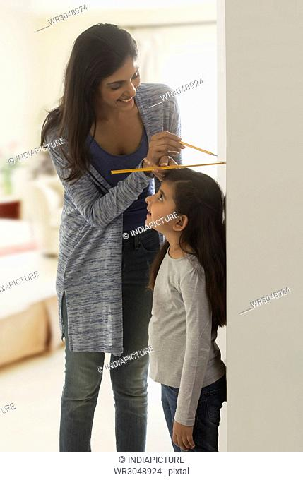 Mother measuring daughter height