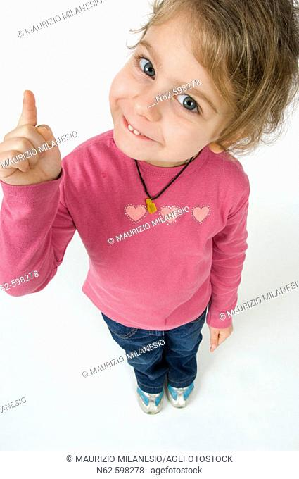 Little girl with facial expression cheerful top view, raises her index finger up