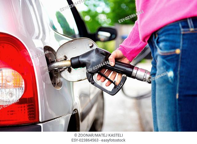 Lady pumping gasoline fuel in car at gas station