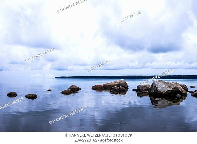Peaceful landscape with rocks and the reflection of clouds in the sea