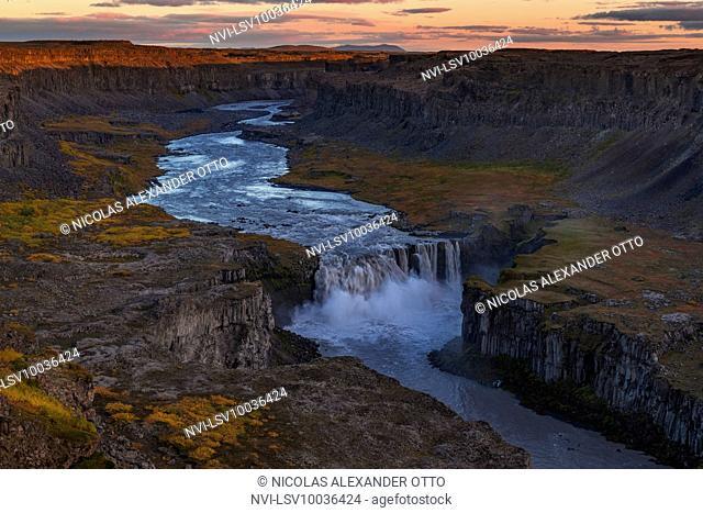 Hafragilsfoss waterfall at sunset and alpine glow in autumn, Jökulsá á Fjöllum, Iceland