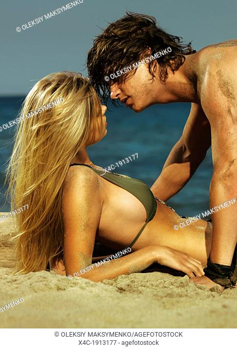 Sensual portrait of a young couple kissing on the beach lying on sand