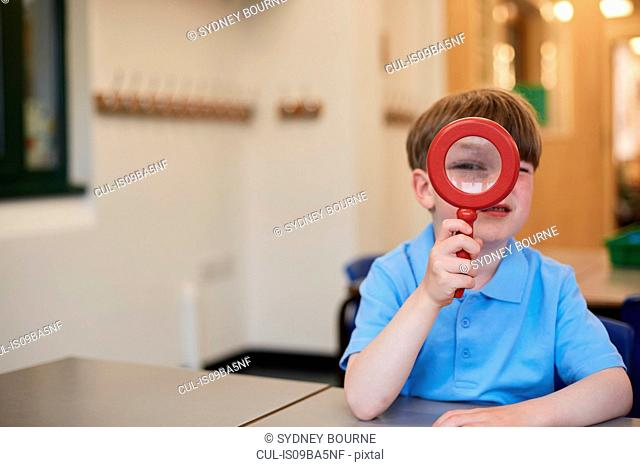 Schoolboy looking through magnifying glass in classroom at primary school, portrait