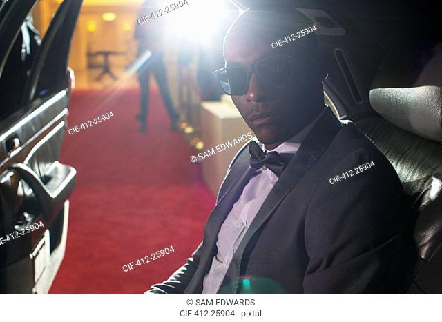 Portrait of serious celebrity in sunglasses inside limousine arriving at red carpet event