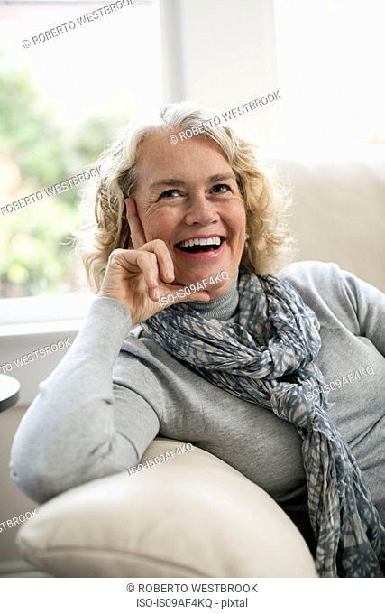 Relaxed senior woman sitting on sofa