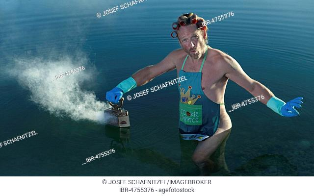 Man with curlers in his hair looking in the water, ironing the water surface with steam iron, Germany