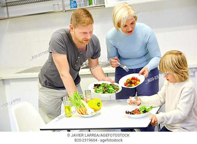 Family in the kitchen. Three generations. Healthy eating. Healthy growth. Making vegetable salad