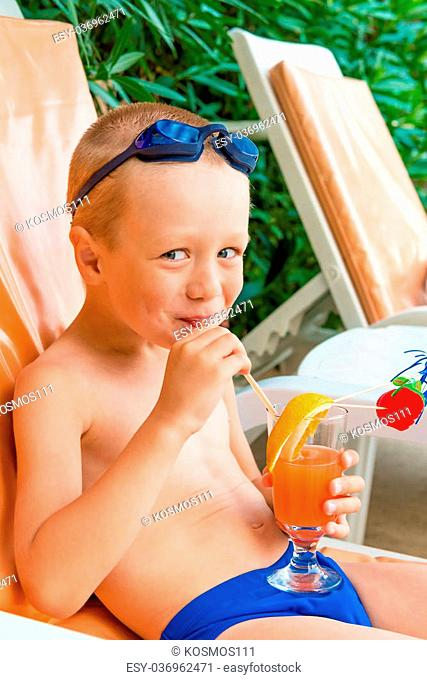 cheerful boy drinks juice at resort