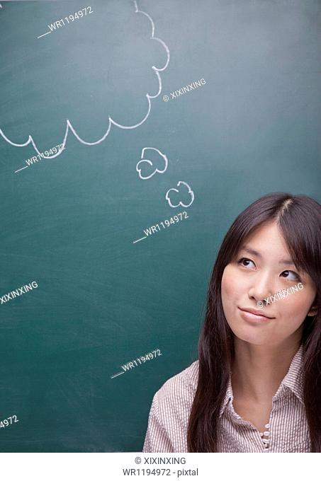 Young woman with thought bubble on blackboard