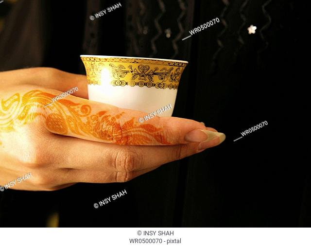 Arab lady henna on hands holding Arabic Coffee cup
