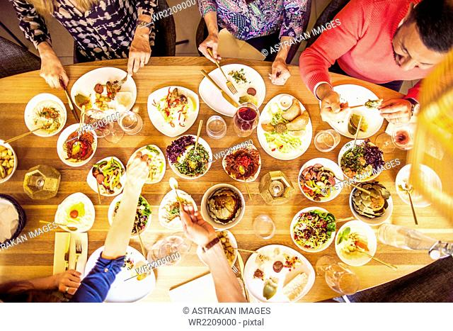 High angle view of male and female friends having meze at table in Lebanese restaurant