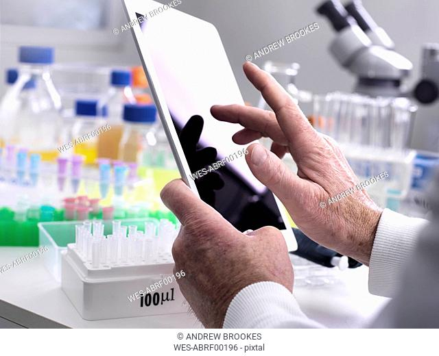 Scientist adding data online via a tablet from a experiment