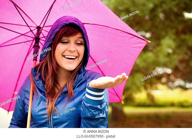Cheerful woman under pink umbrella checking for rain, Debica, Poland