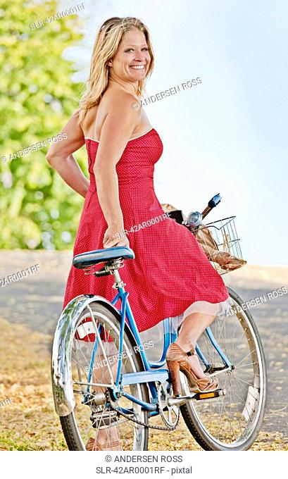 Woman riding bicycle on dirt road