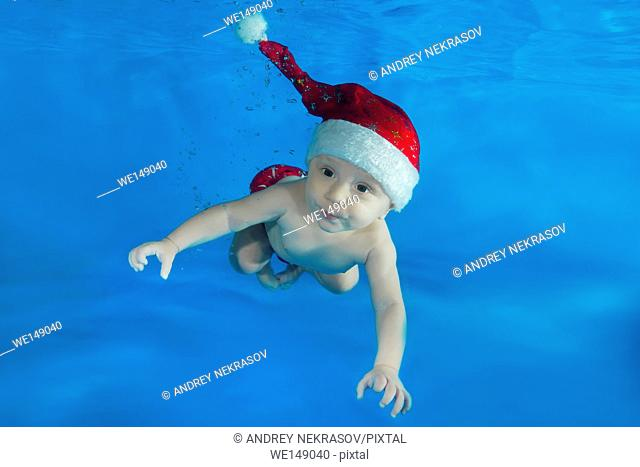 little boy in Santa's red cap floats under water in the pool