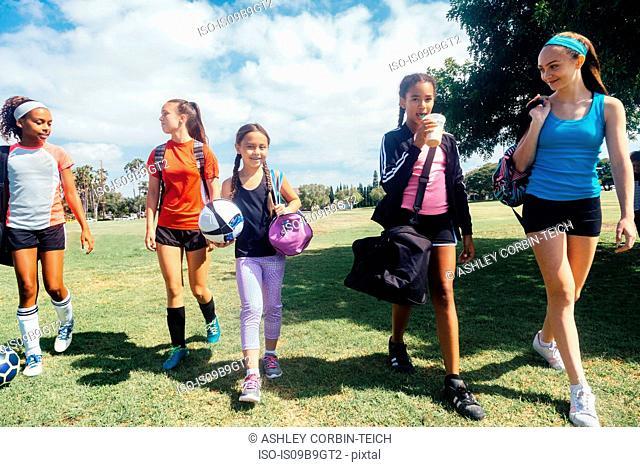 Schoolgirls walking to soccer practice on school sports field