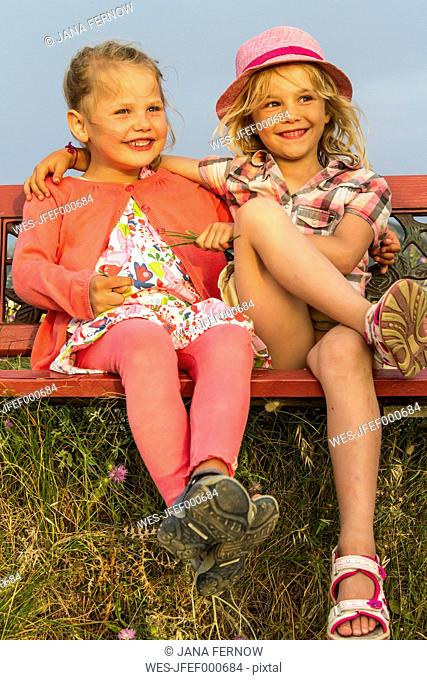 Greece, Corfu, Afionas, two little girls sitting side by side on a bench at evening twilight