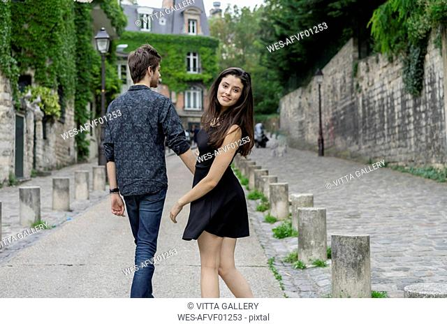 France, Paris, young couple in an alley in the district Montmartre