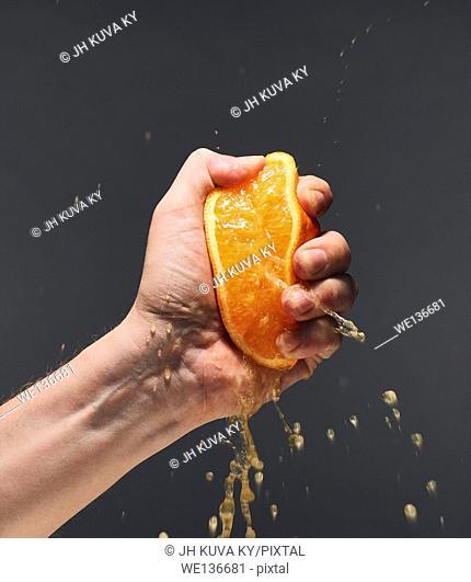 Male hand squeezing juicy orange, dark background