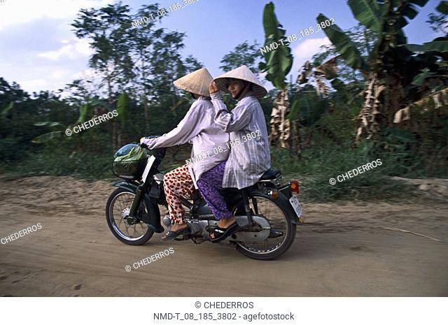 Side profile of two women on a moped, Vietnam