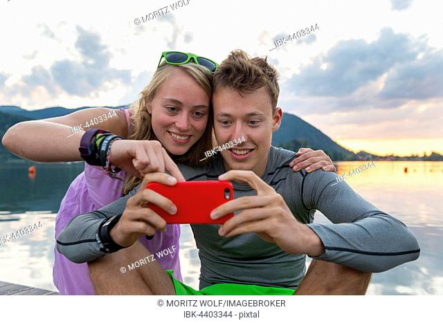 Young couple looking at mobile phone together, Schliersee, Upper Bavaria, Bavaria, Germany
