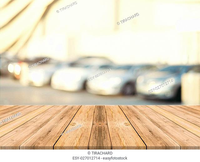 Wooden board empty table blurred background. Perspective brown wood over blur car park outdoor - can be used for display or montage your products