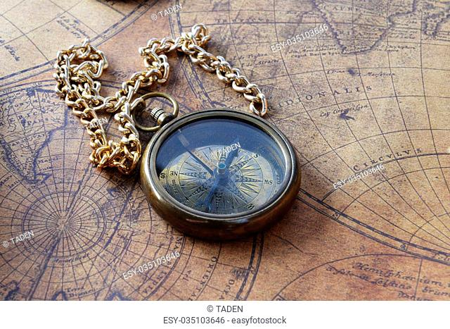 Vintage compass and a pocket watch lying on old map
