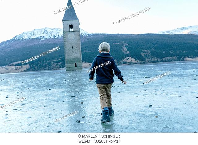 Italy, Venosta Valley, Boy walking on ice to sunken spire in frozen Lago di Resia